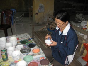 Hand painting bowls at the ceramics factory